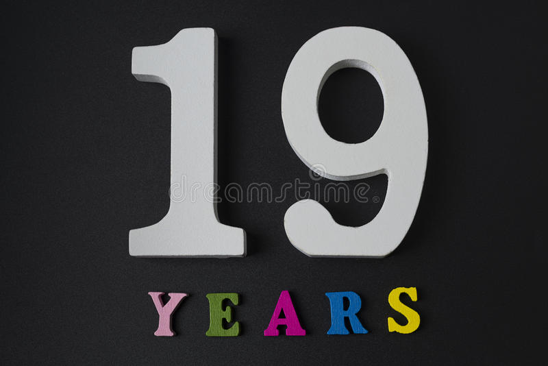 Letras y números diecinueve años en un fondo negro fotografía de archivo