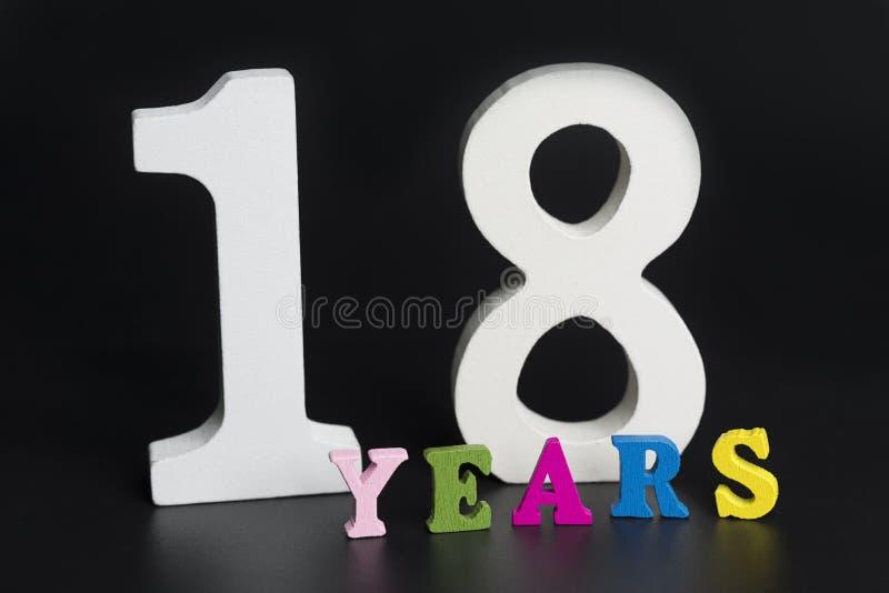 Letras y números por dieciocho años en un fondo negro imagen de archivo libre de regalías
