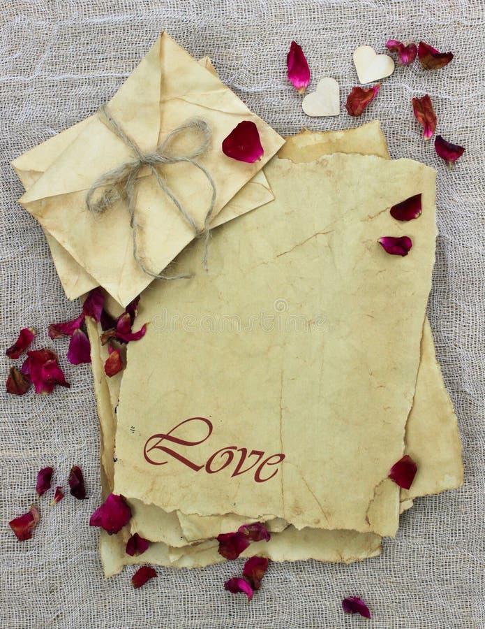 Letras y sobres antiguos de amor del papel de pergamino con los pétalos color de rosa rojos fotos de archivo