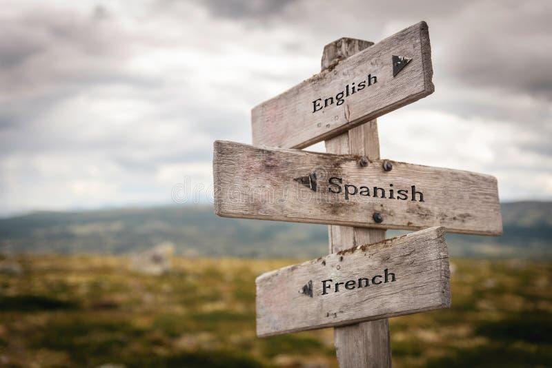 Letreiro de madeira do inglês, o espanhol e o francês fora fotografia de stock royalty free