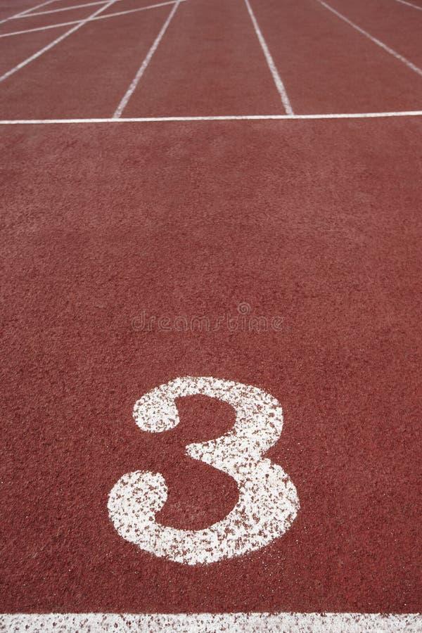 Letreiro do número três em uma pista de atletismo atlética imagem de stock