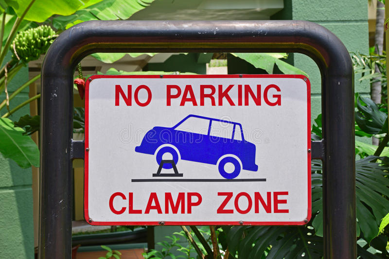 Letrero para la zona del estacionamiento prohibido y de la abrazadera imagen de archivo