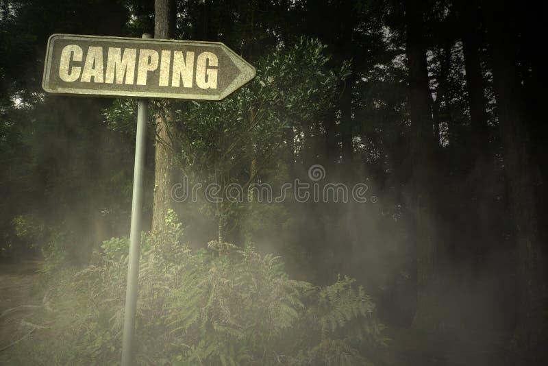 Letrero viejo con el texto que acampa cerca del bosque siniestro imagen de archivo libre de regalías