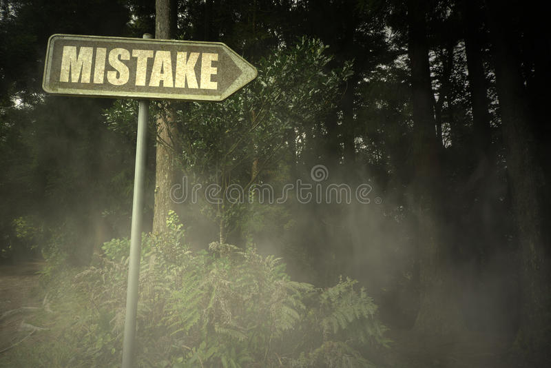 Letrero viejo con error del texto cerca del bosque siniestro foto de archivo