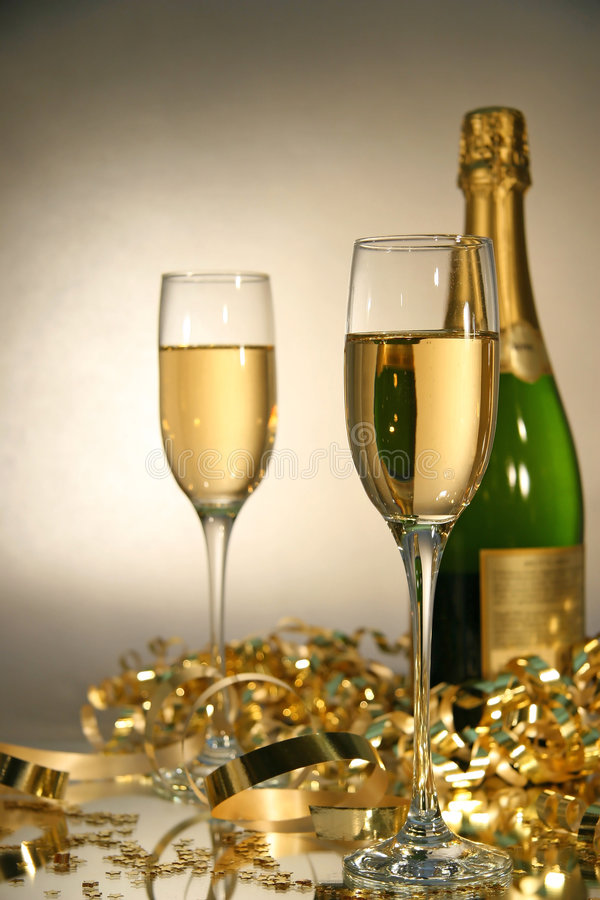 Lets celebrate. Fluted champagne glasses with champagne bottle ready for celebrations royalty free stock images