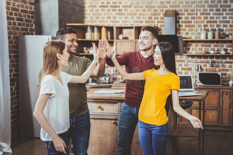 Happy people touching hands with pleasure. Lets celebrate. Delighted females expressing positivity while being at home with boyfriends royalty free stock photography