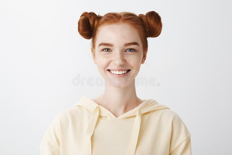 Lets crea algo junto Retrato del primer de la hembra europea encantadora positiva del pelirrojo con el peinado de dos bollos foto de archivo