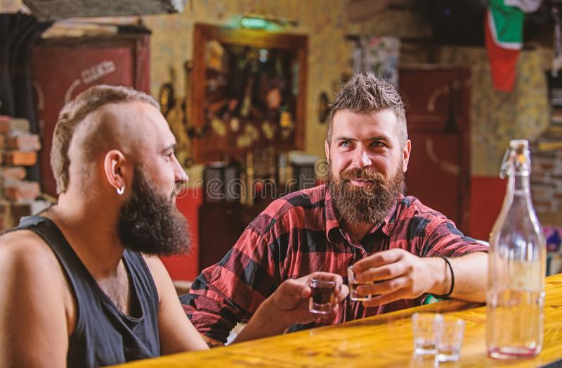 Lets get drunk. Hipster brutal bearded man spend leisure with friend at bar counter. Men relaxing at bar. Strong alcohol stock photos