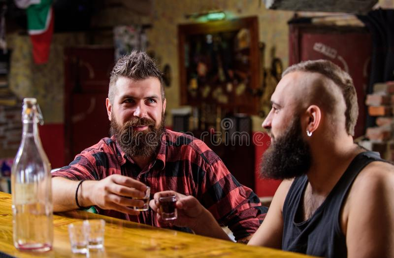 Lets get drunk. Hipster brutal bearded man spend leisure with friend at bar counter. Men relaxing at bar. Strong alcohol stock image