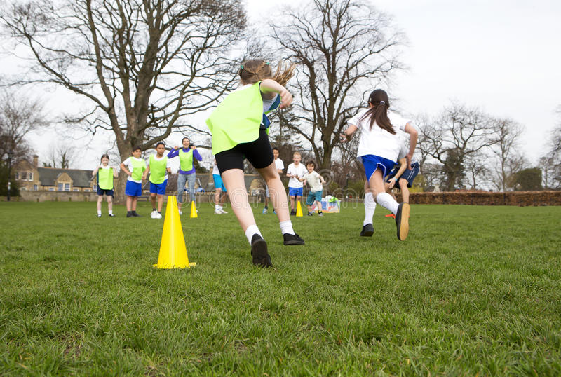 Lets Get Physical. School children wearing sports uniform running around cones during a physical education session stock photography