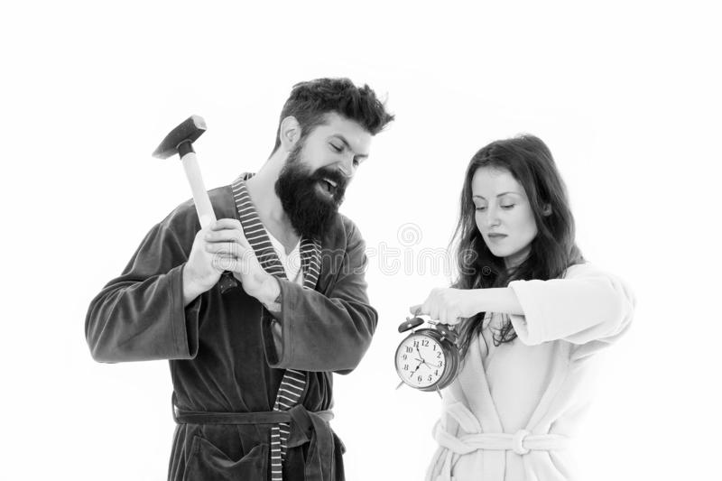Lets get rid of this annoying alarm clock. Couple in bathrobes going to destroy alarm clock and stay at home. Breaking. Rules. Tired of early awakening. Man stock image