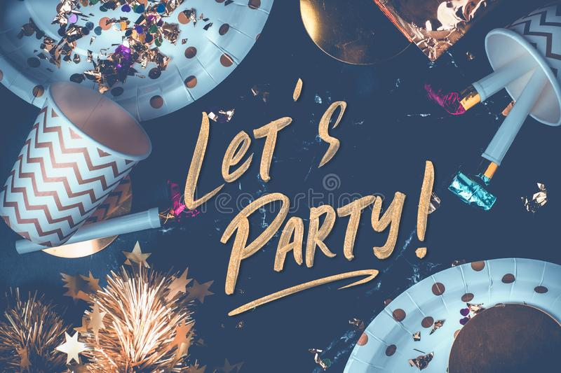 Lets party hand brush stroke font on marble table with party cup,party blower,tinsel,confetti.Fun Celebrate holiday party time. Table top view.blue modern tone royalty free stock images