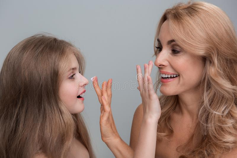 Delightful woman and little girl are testing new lotion. Lets play. Joyful middle-aged mother and her playful kid are standing and applying cream on face of each royalty free stock image