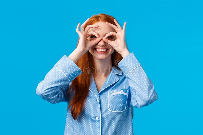 Lets see what do we have here. Excited smiling and carefree pretty young redhead girl in nightwear making glasses or stock photos