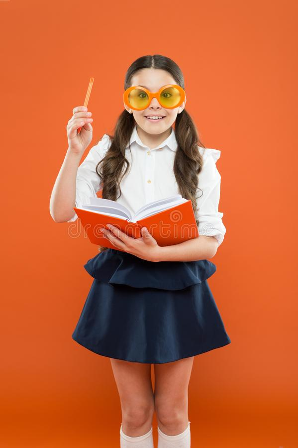 Lets write this idea. children literature. get information from book. happy school girl in uniform and party glasses. Small child with notebook. literature stock image