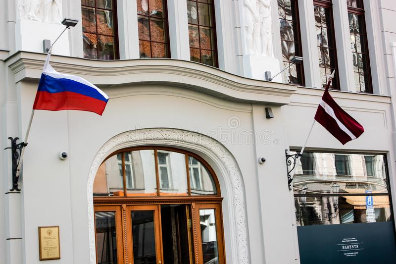 Letse en Russische vlaggen op een neutrale de bouwmuur in Riga stock afbeelding