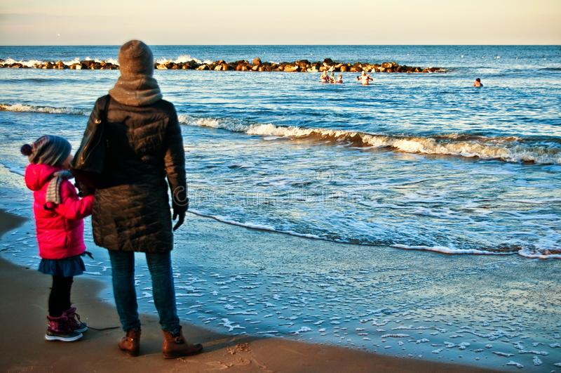Lettende op mensen die in de winteroverzees zwemmen stock fotografie