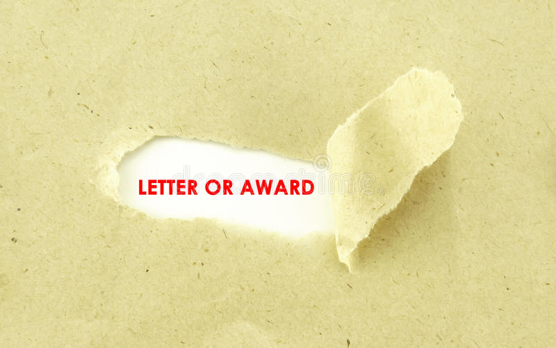 LETTER OF AWARD. Text LETTER OF AWARD appearing behind torn light brown envelope royalty free stock photo