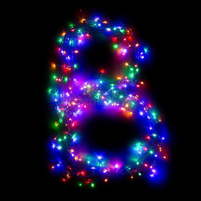 New Year`s alphabet. The letter `B` of the English alphabet from a multi-colored electric garland on a black isolated background. New Year`s alphabet. Wreath of royalty free stock photography