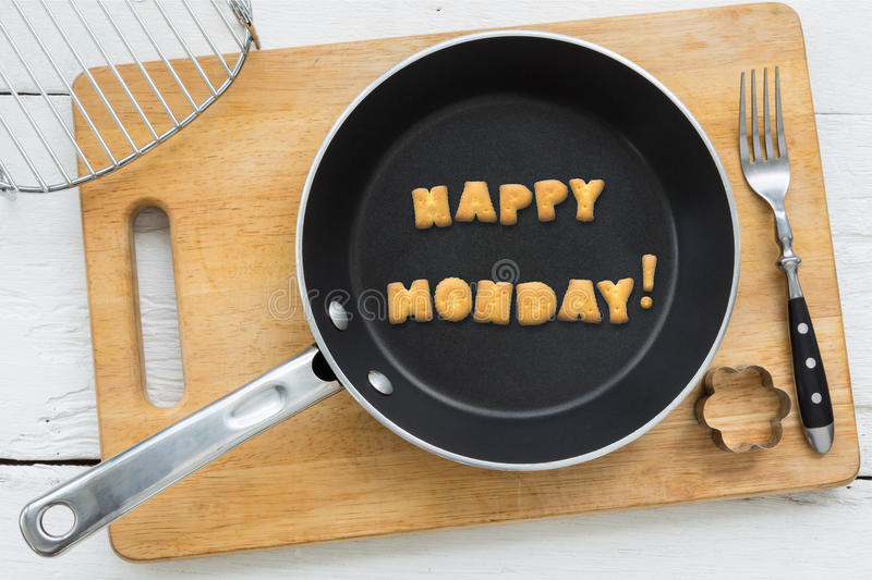 Letter biscuits word HAPPY MONDAY and cooking equipments. Top view of letter collage made of biscuits. Word HAPPY MONDAY putting in black frying pan. Other royalty free stock photography