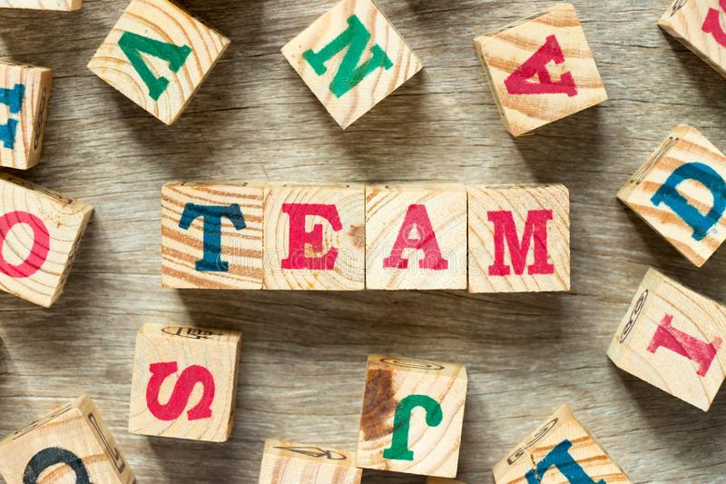 Letter block in word team with another on wood background stock image