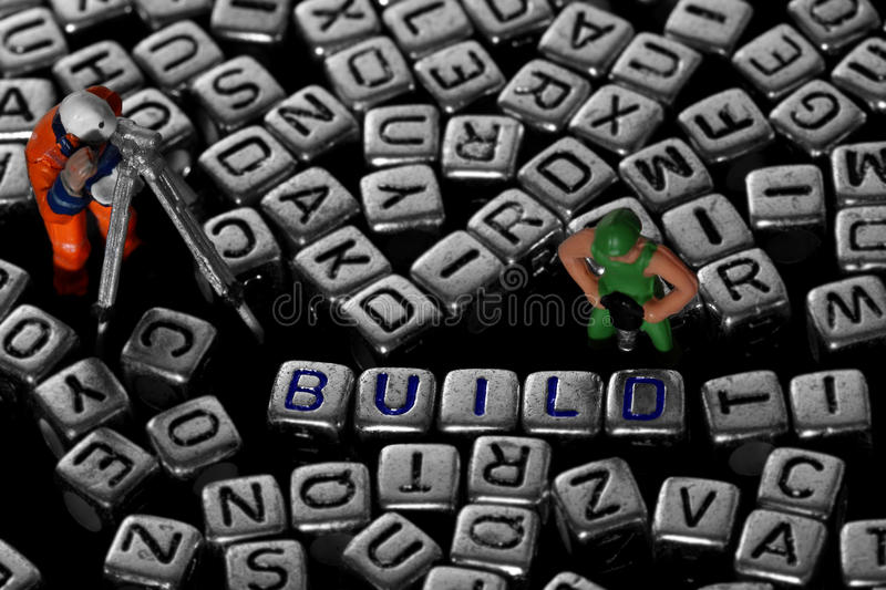 Letter blocks spelling build with model construction workers royalty free stock photos