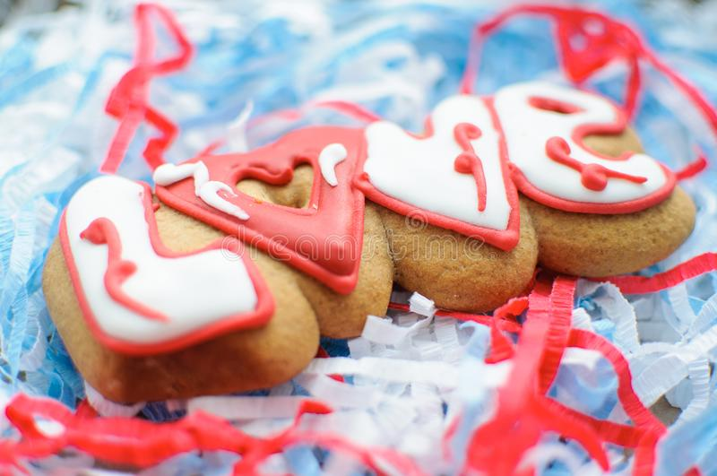 Letter cookies for Valentine`s day or for a wedding day on the blue and white paper filler background. stock image