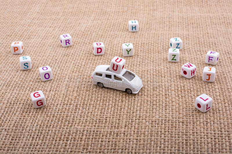 Letter cubes and toy car as a transportation device stock photography