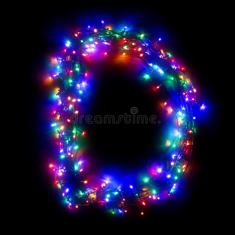 New Year`s alphabet. The letter `D` of the English alphabet from a multi-colored electric garland on a black isolated background. New Year`s alphabet. Wreath of royalty free stock photos