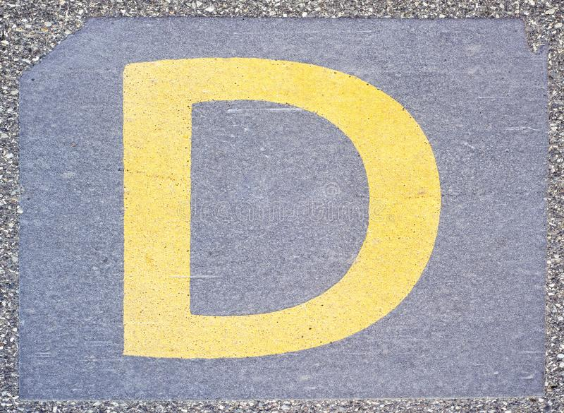 Letter D painted on the concrete pavement stock photos