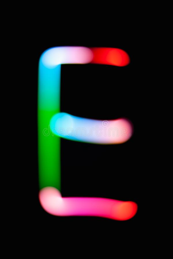 Letter E. Glowing letters on dark background. Abstract light painting at night. Creative artistic colorful bokeh. New Year. Use it for build you own design for stock photo
