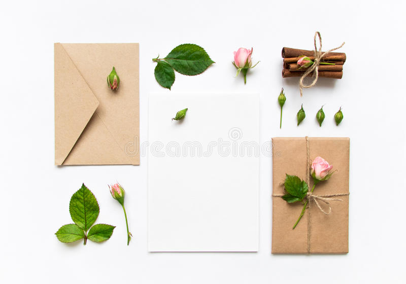 Letter, envelope and gift on white background. Invitation cards, or love letter with pink roses. Holiday concept, top view, flat l. Letter, envelope and a stock photo