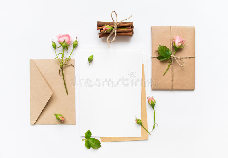 Letter, envelope and gift on white background. Invitation cards, or love letter with pink roses. Holiday concept, top view, flat l. Letter, envelope and a royalty free stock photos