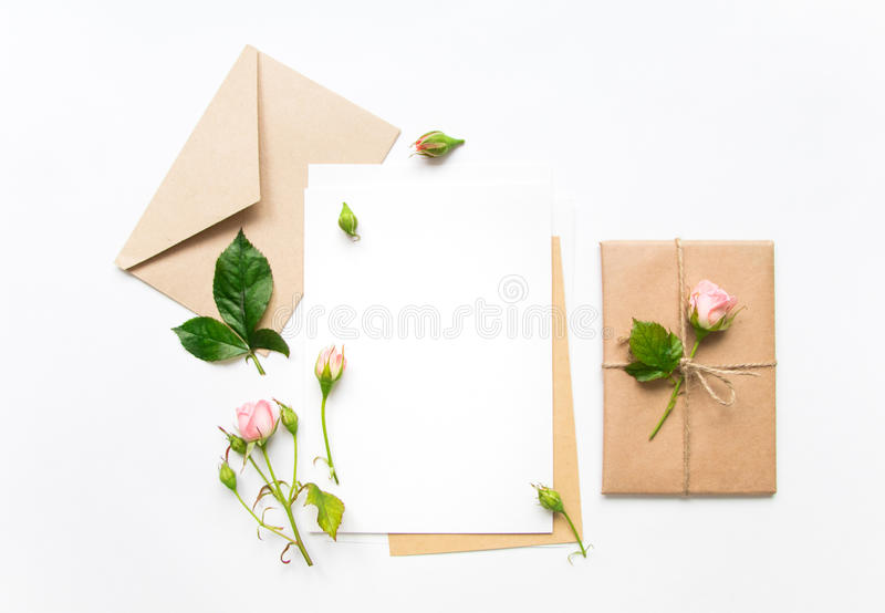 Letter, envelope and gift on white background. Invitation cards, or love letter with pink roses. Holiday concept, top view, flat l. Letter, envelope and a royalty free stock photo