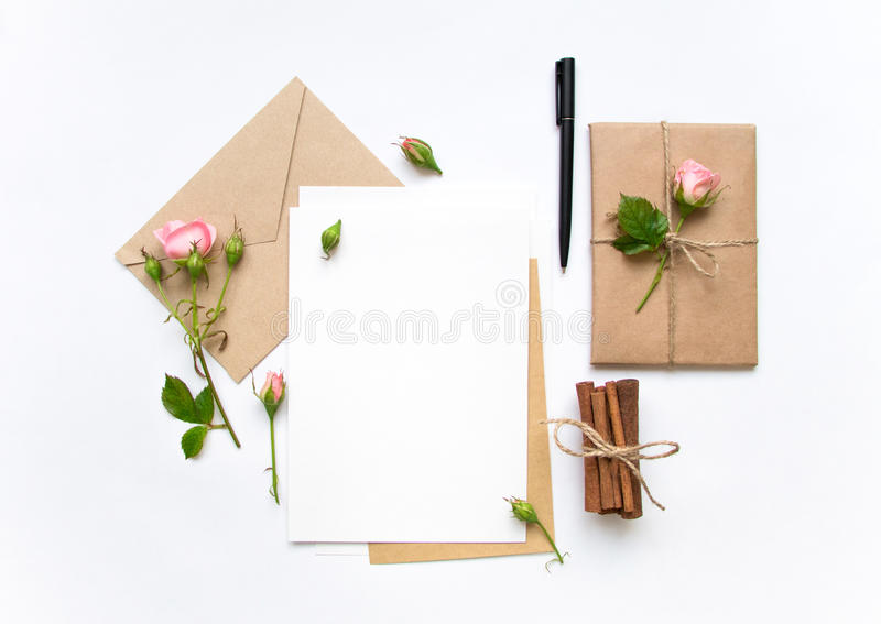 Letter, envelope and gift on white background. Invitation cards, or love letter with pink roses. Holiday concept, top view, flat l. Letter, envelope and a royalty free stock photography