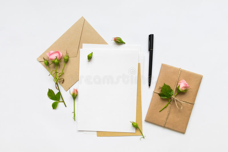 Letter, envelope and gift on white background. Invitation cards, or love letter with pink roses. Holiday concept, top view, flat l. Letter, envelope and a stock images