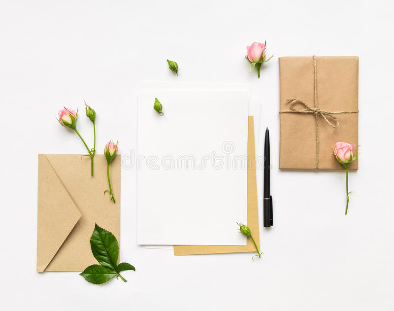Letter, envelope and gift on white background. Invitation cards, or love letter with pink roses. Holiday concept, top view, flat l. Letter, envelope and a stock image