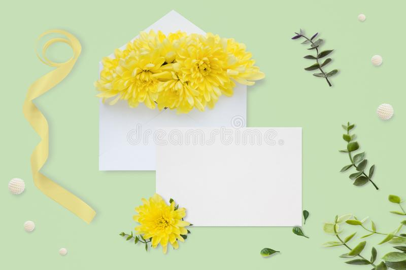 Letter, envelope and a present on pastel green background. Wedding invitation cards or love letter with chrysanthemums. Valentine stock photography