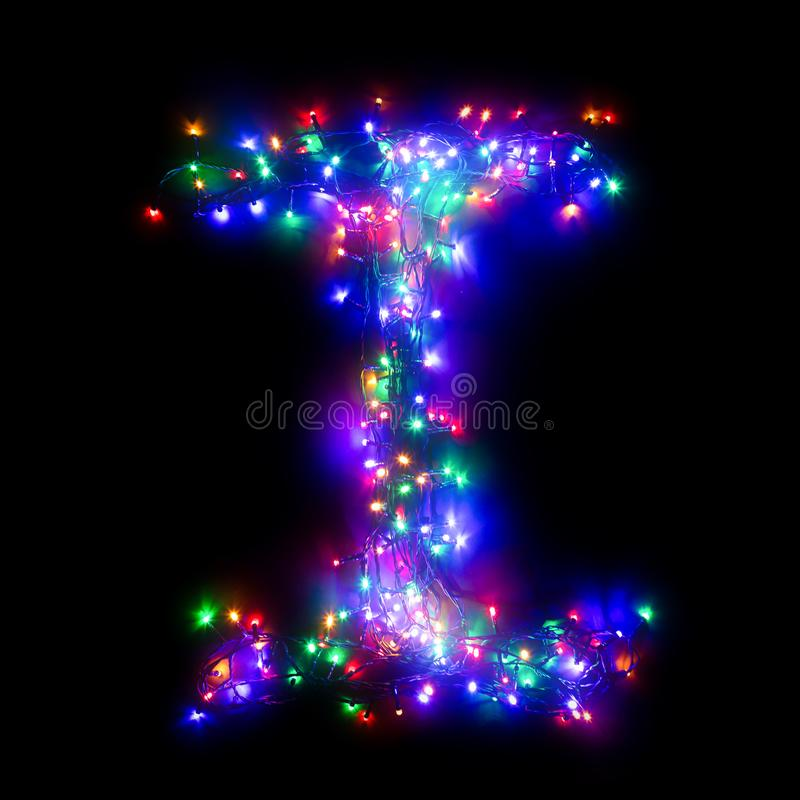 New Year`s alphabet. The letter `I` of the English alphabet from a multi-colored electric garland on a black isolated background. New Year`s alphabet. Wreath of royalty free stock photo