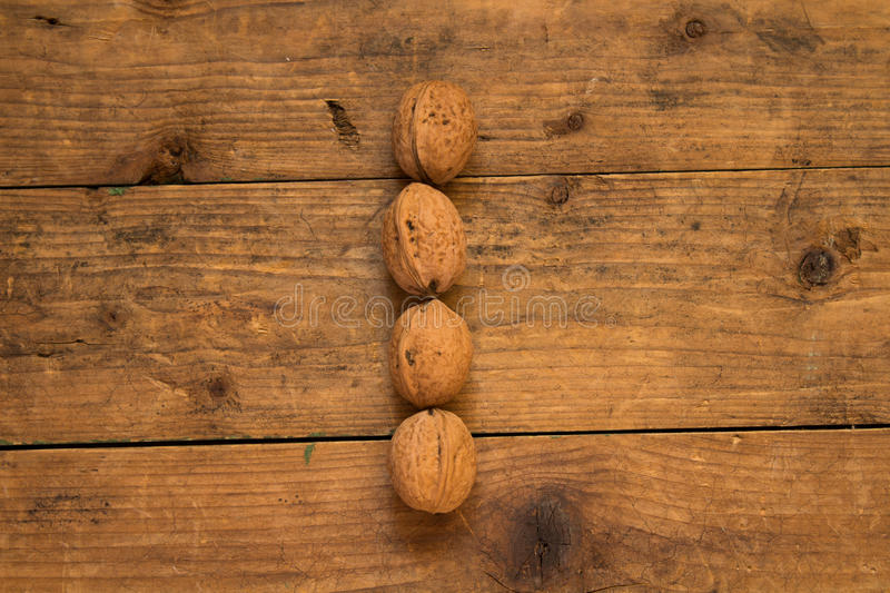 Letter I made from walnuts. Color top view of english alphabet made from walnuts on a wooden table. Letter I royalty free stock image