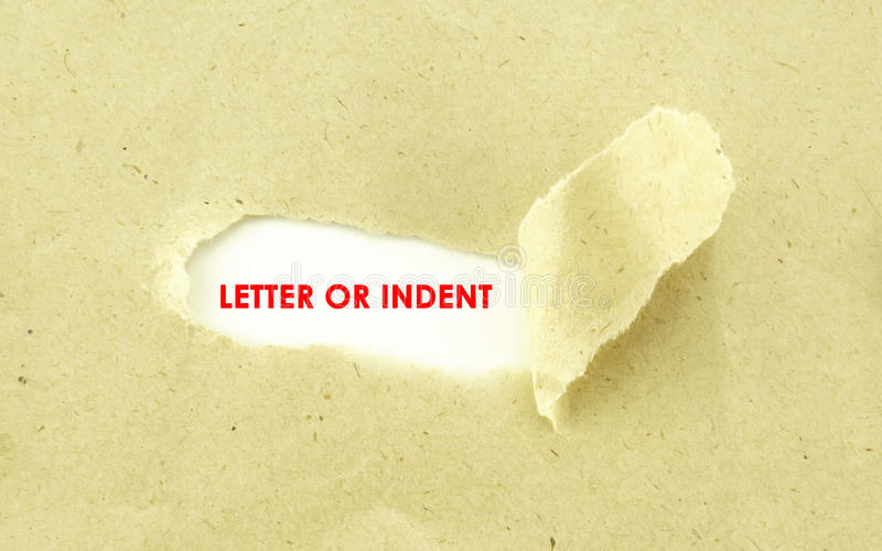 LETTER OF INDENT. Text LETTER OF INDENT appearing behind torn light brown envelope royalty free stock photography