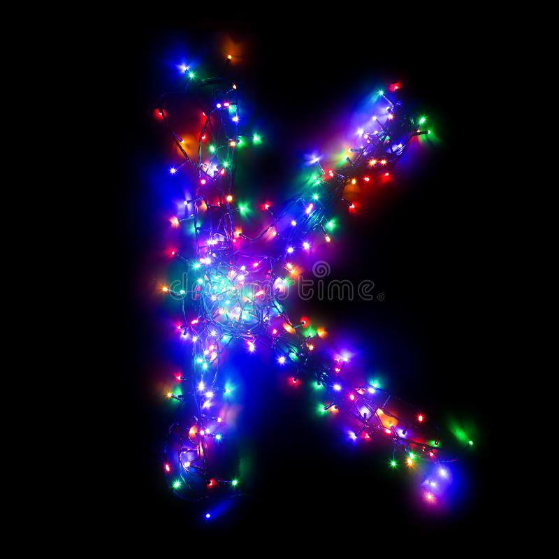 New Year`s alphabet. The letter `K` of the English alphabet from a multi-colored electric garland on a black isolated background. New Year`s alphabet. Wreath of stock photography