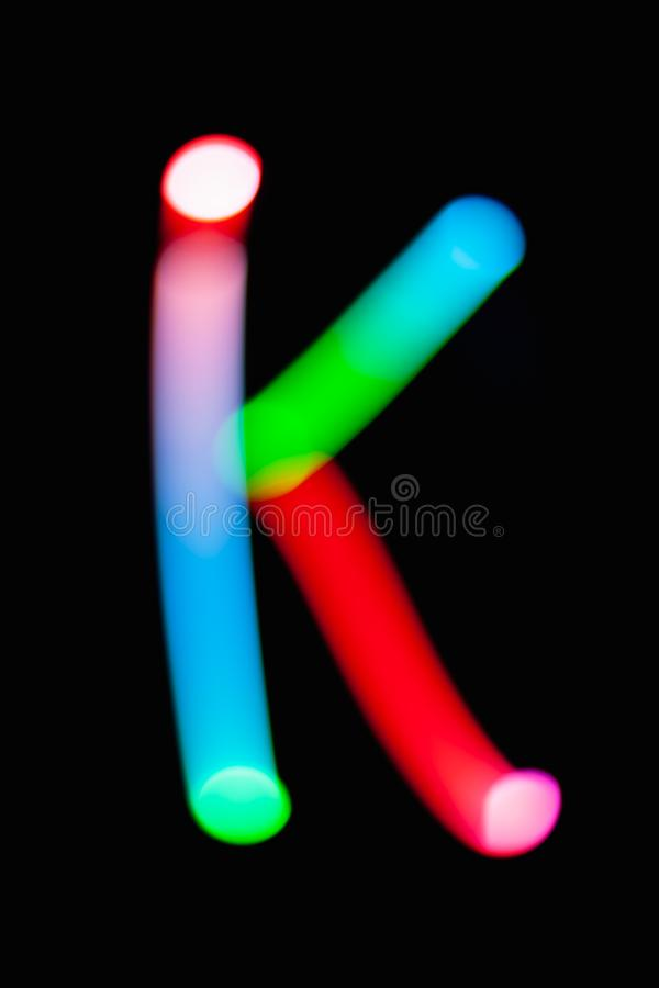 Letter K. Glowing letters on dark background. Abstract light painting at night. Creative artistic colorful bokeh. New Year. Use it for build you own design for stock photos