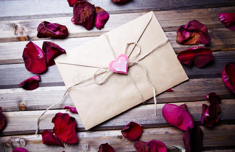 Letter of love. Image of letter of love with small pink heart surrounded by rose petals stock photography