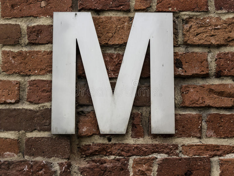 Letter M. Metal letter M on a brick wall royalty free stock photos