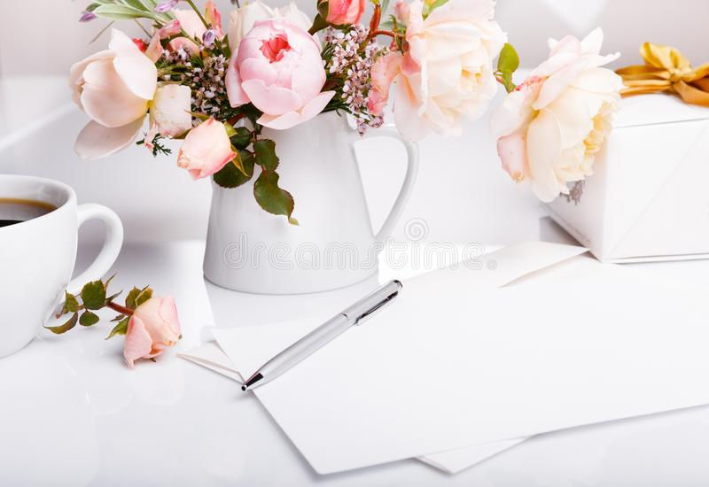 Letter, pen and white envelope on white background with pink english rose. Invitation cards or love letter. Birthday. Cup of coffee, gift, Letter, white envelope royalty free stock photos