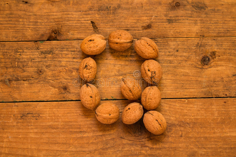 Letter Q made from walnuts. Color top view of english alphabet made from walnuts on a wooden table. Letter Q stock image