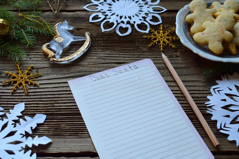 Letter for Santa Claus. Wish list. Christmas decoration, paper snowflakes, gingerbread man on wooden background. Winter holiday co. Ncept. Top view, copy space stock photo