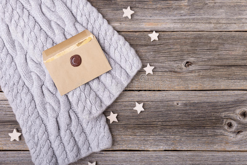 Letter and scarf on wooden boards. Winter scarf and the letter on the background of the old wooden boards stock image