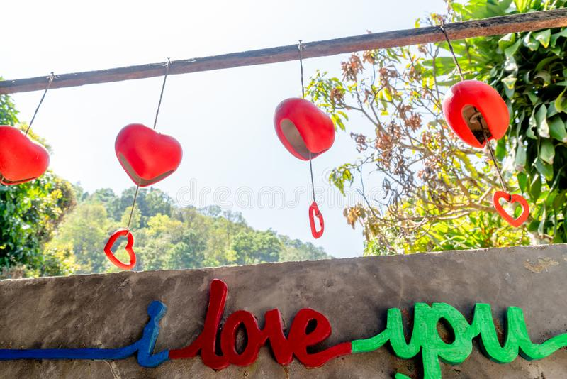 Letter sign says `I love you` and red heart mobile decoration. royalty free stock images
